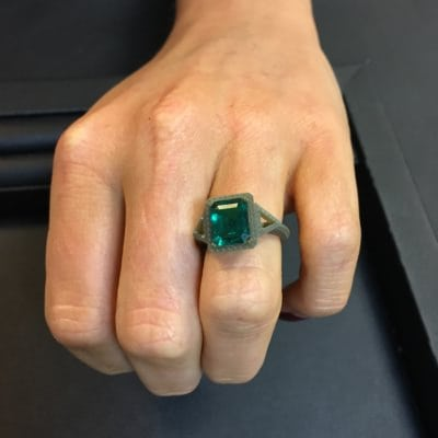 client trying on a wax ring ring with an emerald resting in it